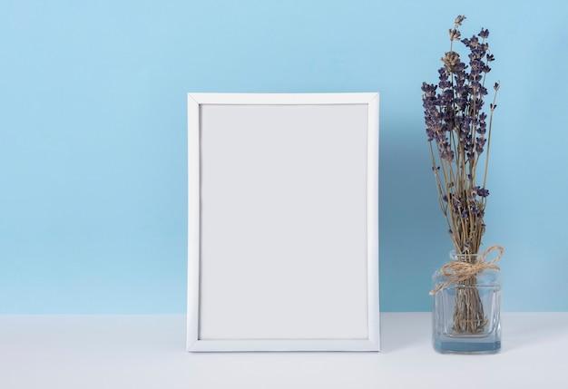 Verticale emply lente witte fotolijst mockup op een blauwe achtergrond met lavendelbloemen in een vaas. vrouwendag concept. Premium Foto