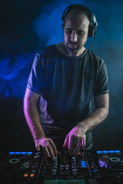 Verticale foto van een mannelijke dj onder de blauwe lichten en rook Gratis Foto
