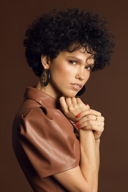Verticale foto van een vrouwelijk model met krullen in een studio in bruine tinten. hoge kwaliteit foto Premium Foto