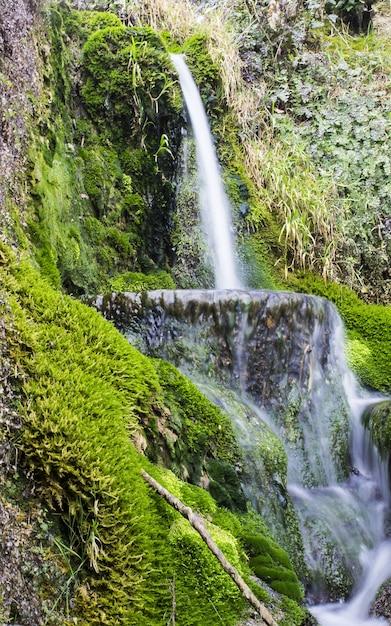 Verticale foto van een waterval omgeven door groen onder het zonlicht in het nationaal park krka Gratis Foto