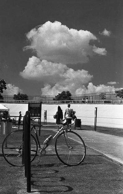 Verticale grijsschaal die van een fiets is geparkeerd die dichtbij een sportarena wordt geparkeerd Gratis Foto