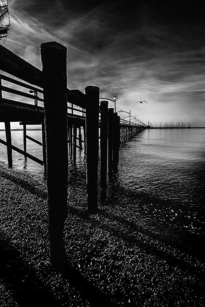 Verticale grijswaarden shot van een houten dok met kolommen op het meer onder de prachtige onweerswolken Gratis Foto