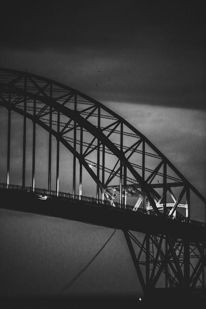 Verticale grijswaarden shot van een moderne ijzeren boogvormige brug Gratis Foto