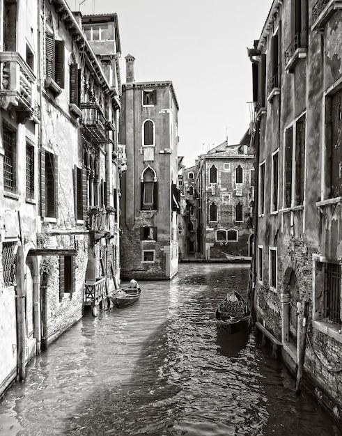Verticale grijswaardenopname van een kanaal in het historische district van venetië, italië Gratis Foto
