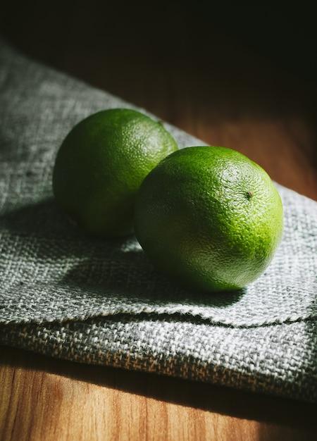 Verticale hoge hoek close-up shot van twee hele limoenen op een houten tafel Gratis Foto