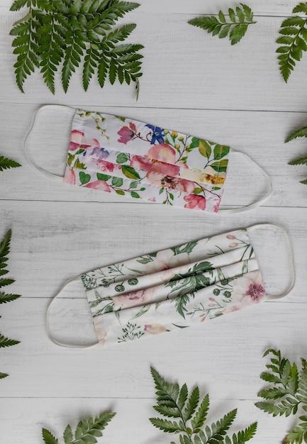 Verticale hoge hoek opname van gezichtsmaskers met bloemenmotief en groene bladeren op een houten oppervlak Gratis Foto