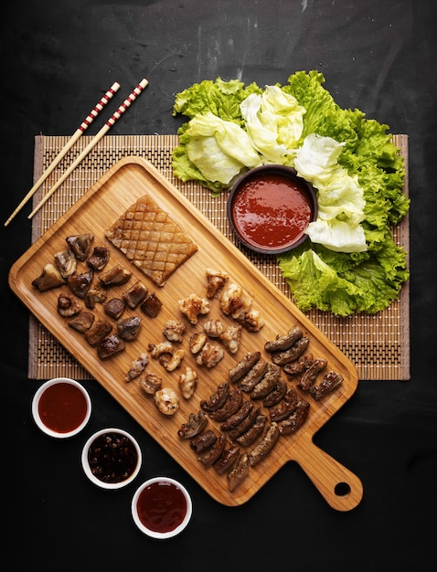Verticale hoge hoek shot van een bakje met gebakken vlees en aardappelen en saus en groenten Gratis Foto