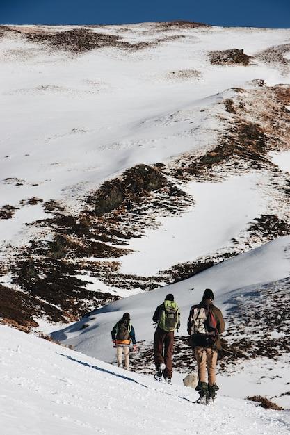 Verticale hoge hoek shot van wandelaars met rugzakken in de besneeuwde bergen Gratis Foto
