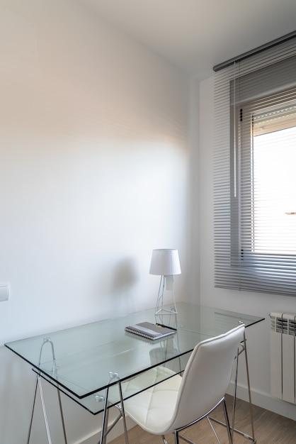 Verticale hoge hoekopname van een minimalistische witte kamer met een glazen bureau bij het raam Gratis Foto