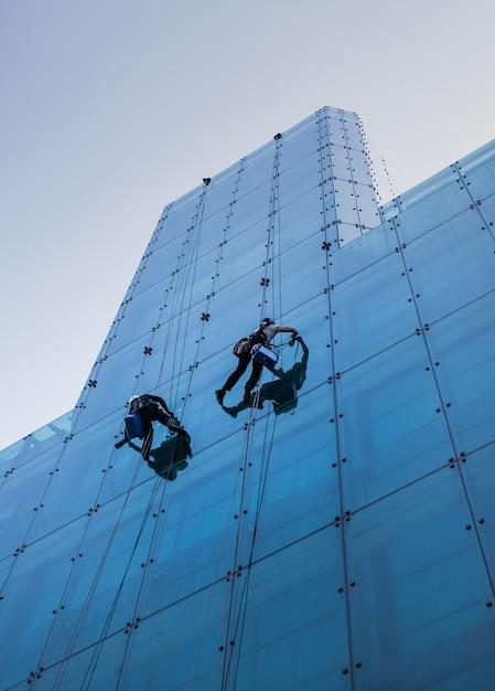 Verticale lage hoek die van twee mensen is ontsproten die overdag een hoog glazen gebouw beklimmen Gratis Foto