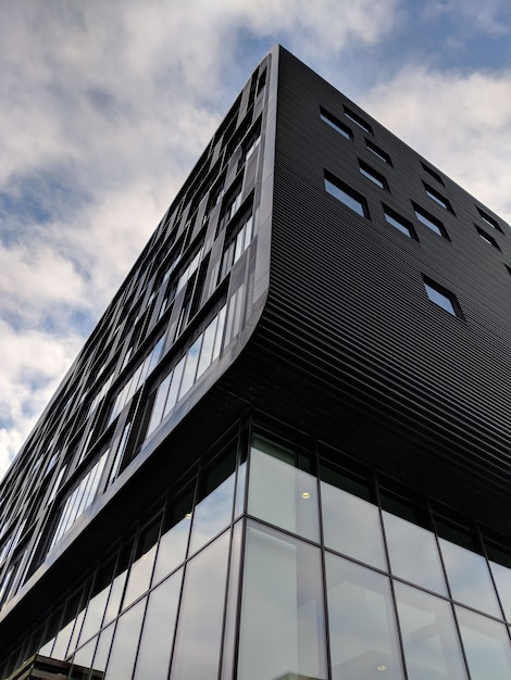 Verticale lage hoek shot van een hoogbouw zwart gebouw met glazen ramen Gratis Foto