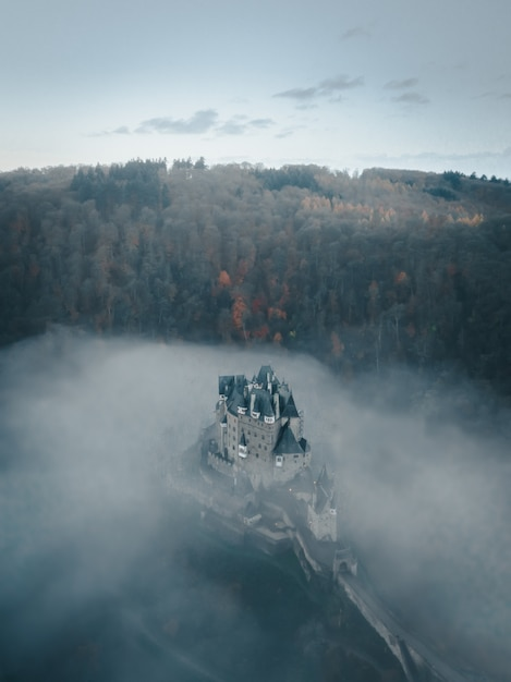 Verticale luchtfoto van het kasteel eltz omgeven met wolken en bomen in duitsland Gratis Foto
