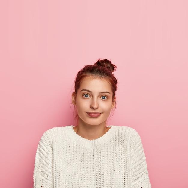 Verticale opname van aangenaam ogende tevreden duizendjarige meisje draagt casual gebreide trui, heeft volle lippen en blauwe ogen, donker haar gekamd in knoop, poses op roze achtergrond, lege ruimte erboven Gratis Foto