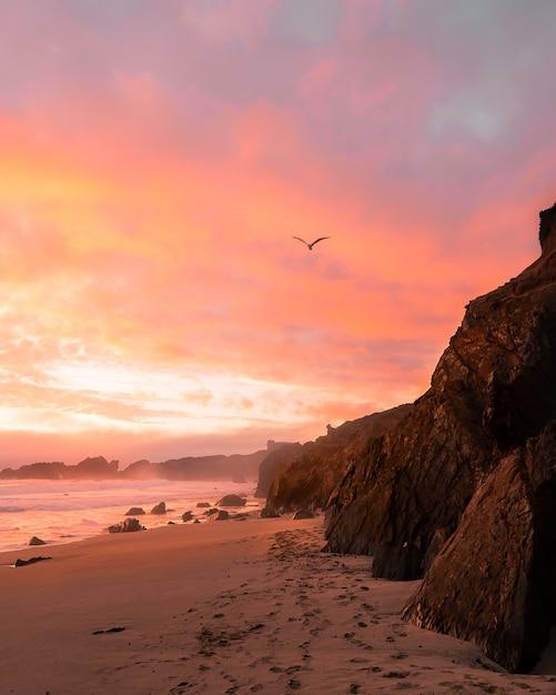 Verticale opname van de bergen op het strand tijdens zonsondergang Gratis Foto