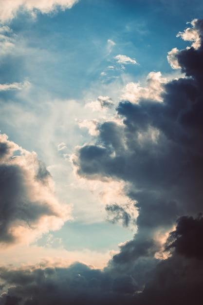 Verticale opname van de pluizige witte wolken die samenkomen in de lucht Gratis Foto