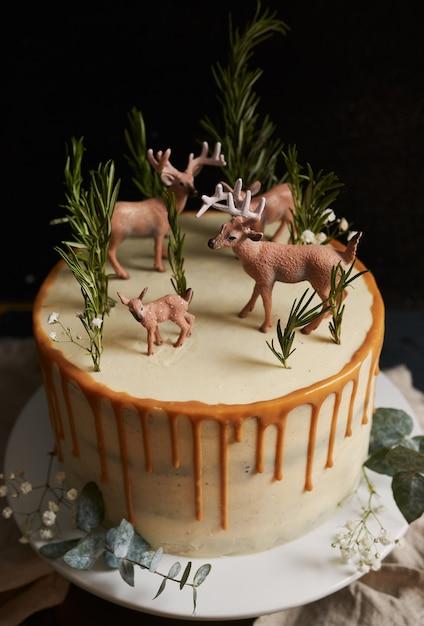 Verticale opname van een dromerige cake met witte room en oranje infuus met een bos en rendieren erop Gratis Foto