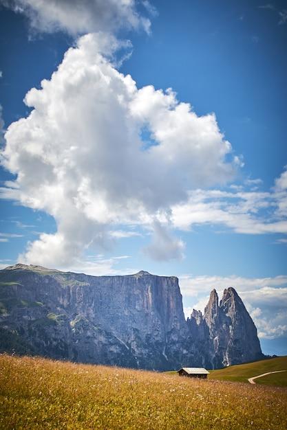 Verticale opname van een hut in een grasveld omgeven door hoge rotswanden in italië Gratis Foto