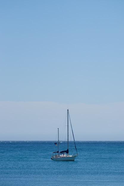Verticale opname van een kleine boot die in de oceaan vaart met een heldere blauwe lucht Gratis Foto