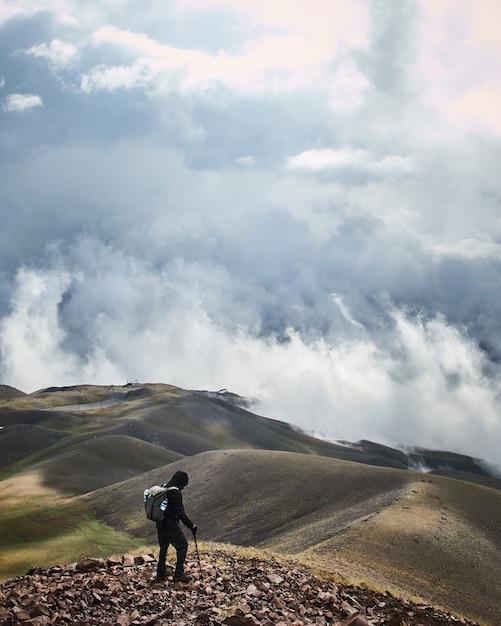 Verticale opname van een mannetje dat op een berg met een bewolkte hemel op de achtergrond staat Gratis Foto