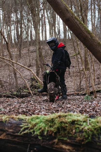 Verticale opname van een motorrijder die zich klaarmaakt voor een rit in een bos Gratis Foto
