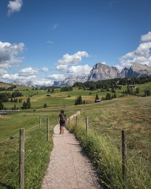 Verticale opname van een persoon die over een onverharde weg loopt met de plattkofel-berg Gratis Foto