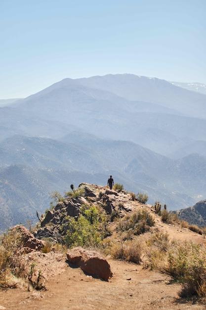 Verticale opname van een persoon die terugloopt vanaf de rand van een berg in de verte Gratis Foto
