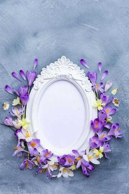 Verticale opname van een sierlijke wit frame met paarse en witte lentebloemen Gratis Foto