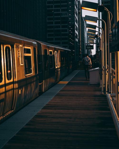Verticale opname van een treinstation met de trein tijdens de zonsopgang Gratis Foto