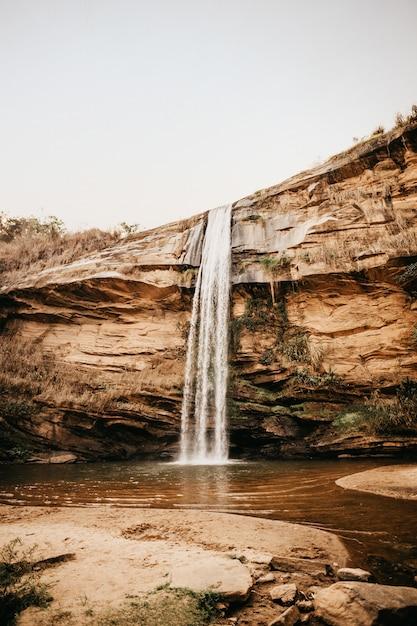 Verticale opname van een waterval die overdag van een lage klif in een klein grasveld stroomt Gratis Foto