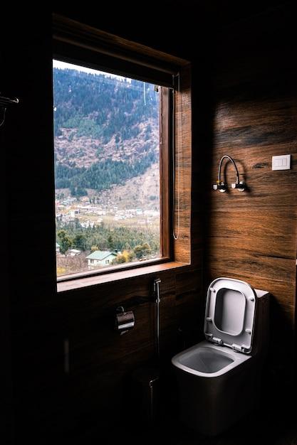 Verticale opname van een wc-bril bij het raam met het prachtige uitzicht op een landschap Gratis Foto