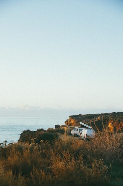 Verticale opname van een wit busje in de buurt van een klif aan zee overdag Gratis Foto
