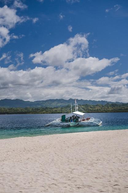 Verticale opname van een witte boot op het strand achter de bergen Gratis Foto