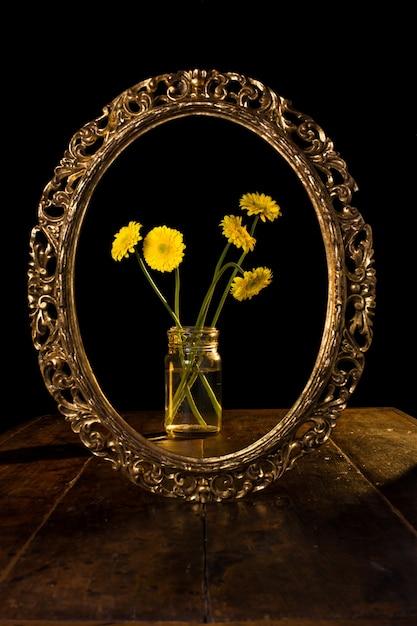 Verticale opname van gele bloemen in een glazen pot weerspiegeld in de spiegel Gratis Foto