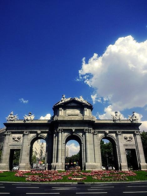 Verticale opname van het neoklassieke monument puerta de alcala in madrid onder een blauwe hemel Gratis Foto