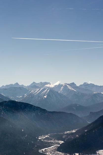 Verticale opname van prachtige bergketens onder een heldere hemel met motorroutes Gratis Foto
