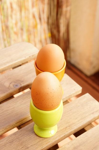 Verticale opname van twee eieren in kopjes op een houten tafel Gratis Foto