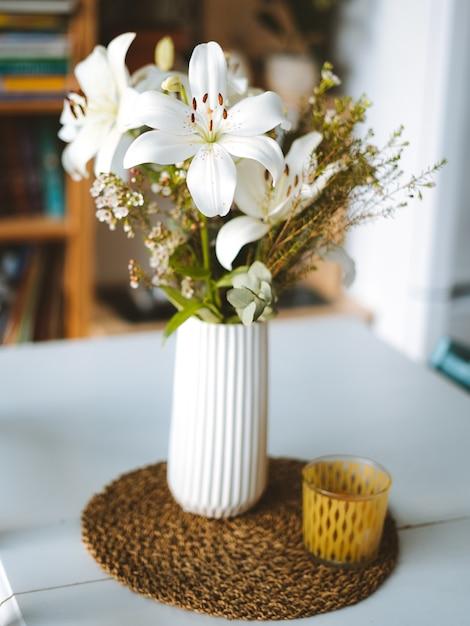 Verticale opname van witte orchideeën in een vaas op een tafel in een kamer in madeira, portugal Gratis Foto