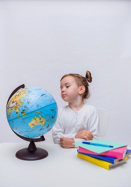 Verticale oriëntatie. een slimme studente zit aan een tafel en kijkt naar een wereldbol op een geïsoleerd wit Premium Foto