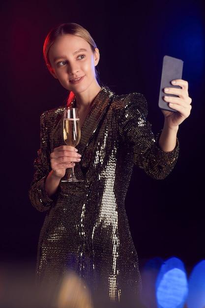 Verticale portret van blonde jonge vrouw livestreaming of selfie foto nemen terwijl u geniet van feest in nachtclub Premium Foto