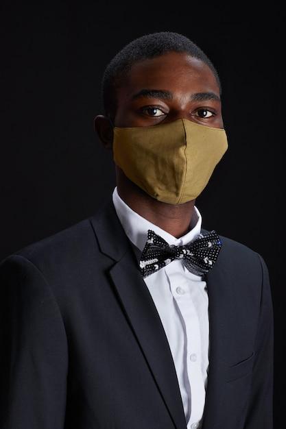Verticale portret van elegante afro-amerikaanse man met gezichtsmasker terwijl poseren tegen zwarte achtergrond op feestje Premium Foto