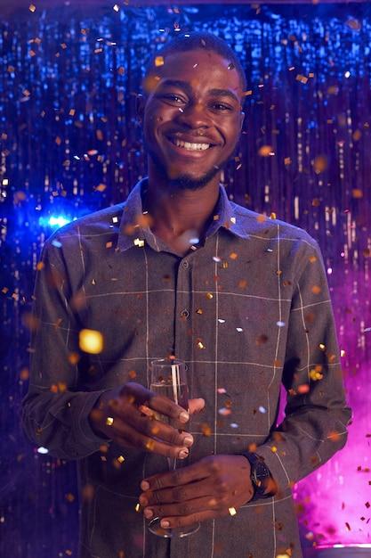 Verticale portret van jonge afro-amerikaanse man champagne glas te houden en glimlachend in de camera terwijl u geniet van feest in nachtclub Premium Foto