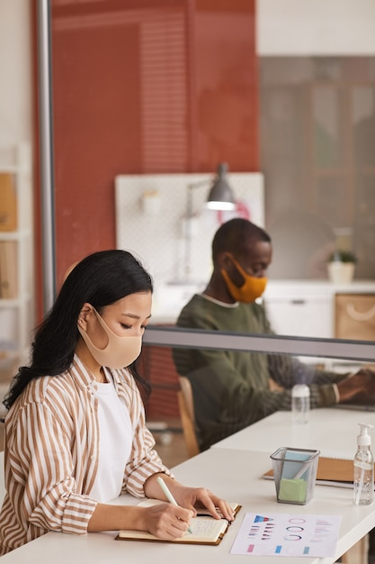 Verticale portret van moderne aziatische zakenvrouw masker dragen en schrijven in planner tijdens het werken in een kantoorcel Premium Foto