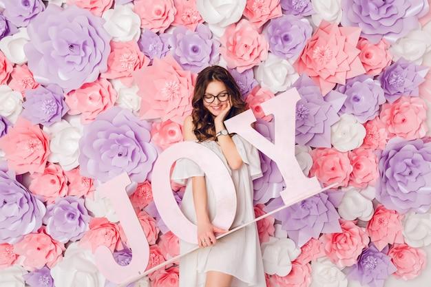 Verticale portret van schattig brunette meisje. ze staat op en houdt het houten woord joy breed glimlachend vast. achtergrond in roze bloemen Gratis Foto