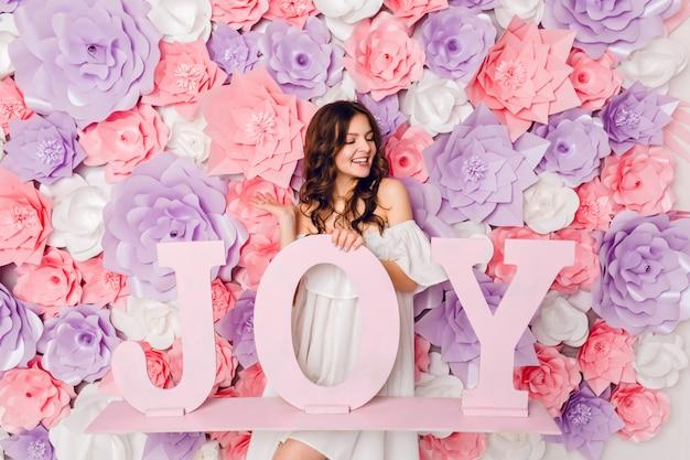 Verticale portret van schattig brunette meisje. ze staat op en houdt het houten woord joy breed glimlachend vast. ze heeft een roze achtergrond bedekt met bloemen Gratis Foto