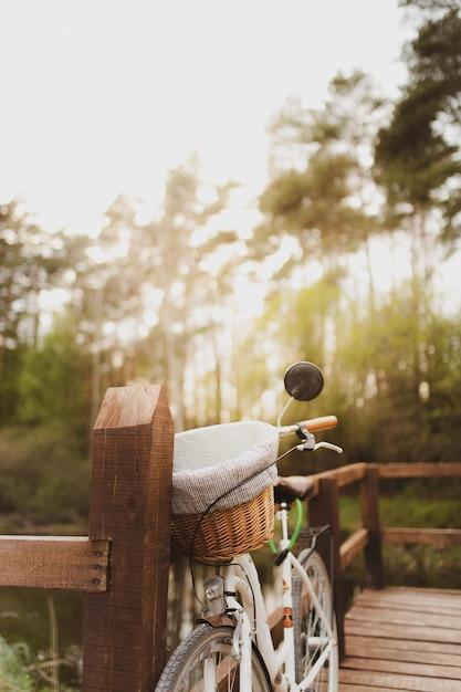 Verticale shot van een fiets geparkeerd op een houten brug in het bos Gratis Foto