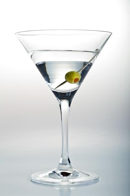 Verticale shot van een glas martini en een olijf erin op wit Gratis Foto