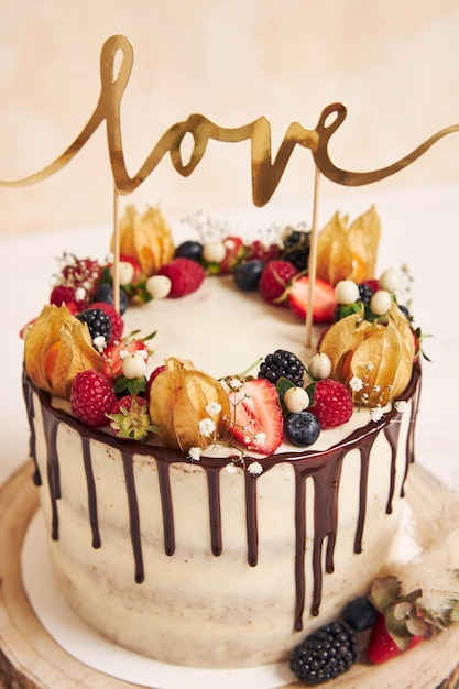 Verticale shot van een prachtige bruidstaart met fruit chocolade infuus en met love topper Gratis Foto