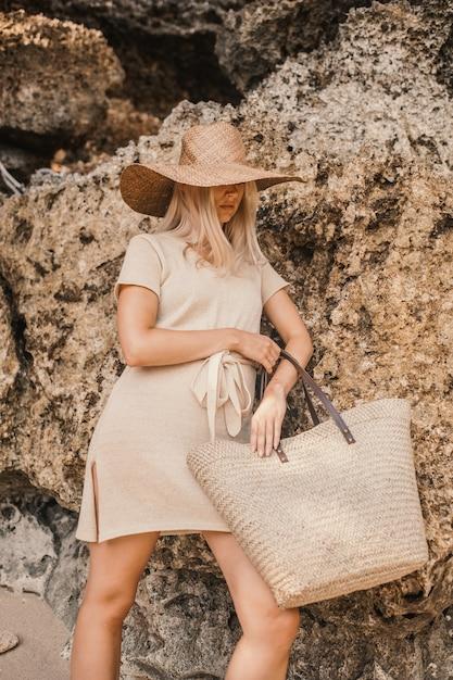Verticale shot van een stijlvolle blonde aantrekkelijke vrouw poseren naast de kliffen overdag Gratis Foto