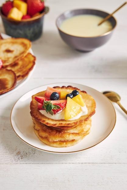 Verticale shot van heerlijke pannenkoeken met fruit op de top bij het ontbijt Gratis Foto