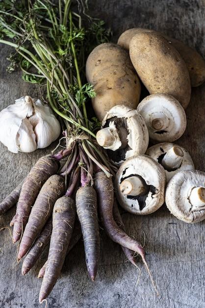 Verticale shot van knoflook, aardappelen, champignons en wortelen op een houten oppervlak Gratis Foto